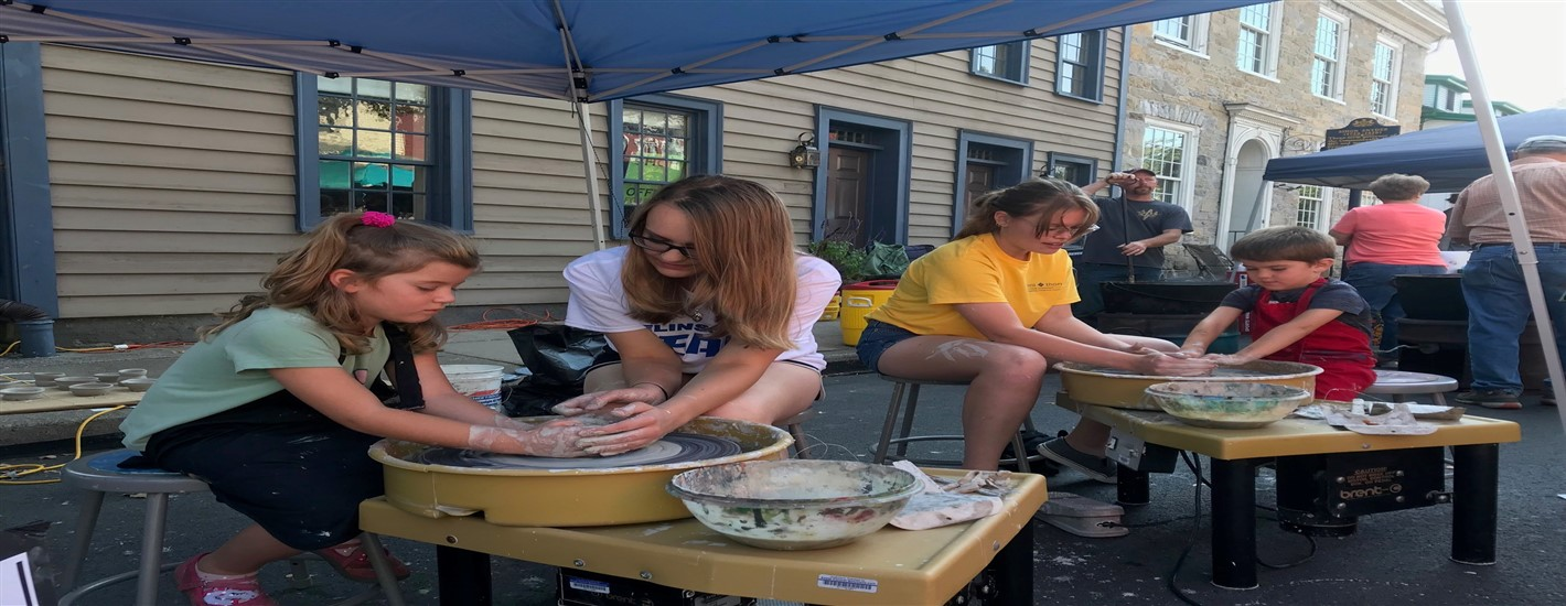 Jilia Pannebaker and Sydney Bower from the National Art Honor Society at the Market Street Festival Helping Elementary Students with the Pottery Wheel
